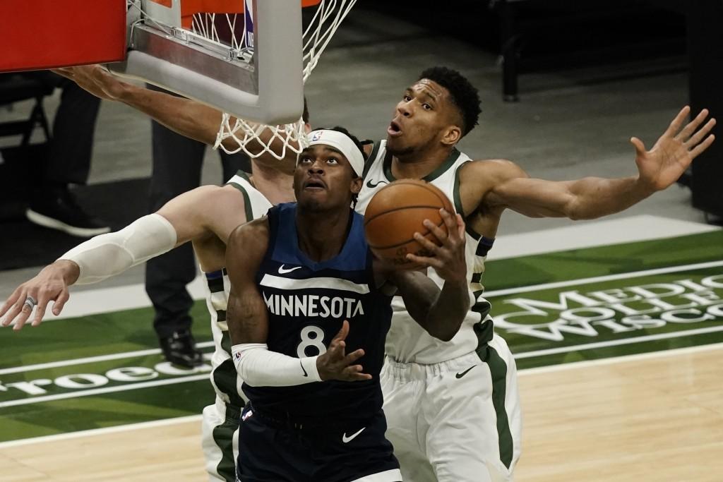 Minnesota Timberwolves' Jarred Vanderbilt shoots past Milwaukee Bucks' Giannis Antetokounmpo during the first half of an NBA basketball game Tuesday, ...