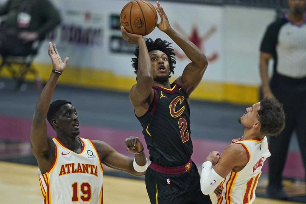 Cleveland Cavaliers' Collin Sexton (2) shoots against Atlanta Hawks' Tony Snell (19) and Trae Young (11) in the first half of an NBA basketball game, ...
