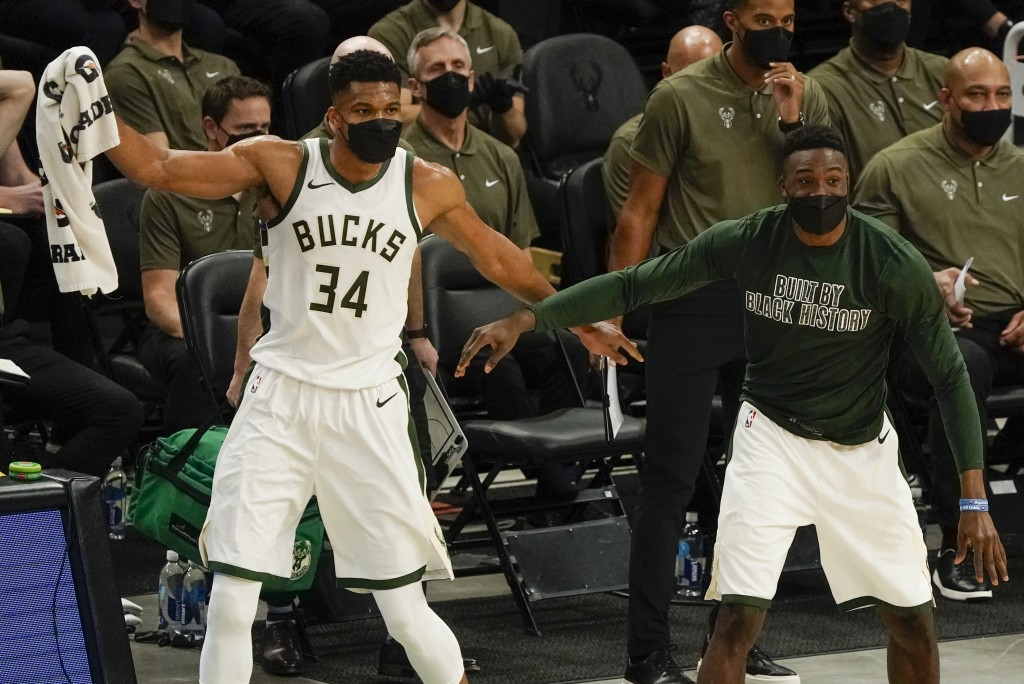 Milwaukee Bucks' Giannis Antetokounmpo and Thanasis Antetokounmpo reacts after teammate Donte DiVincenzo made a three-point basket during the first ha...