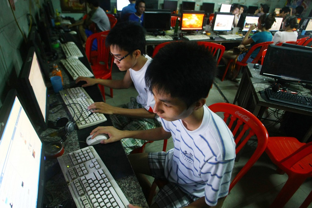 In this Sept. 27, 2012, file photo, two students use computers at an internet cafe near their dormitory in Hanoi, Vietnam. Amnesty International has f...