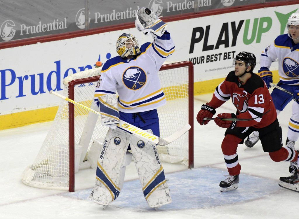 Buffalo Sabres goaltender Linus Ullmark (35) gloves the puck as New Jersey Devils center Nico Hischier (13) looks on during the first period of an NHL...