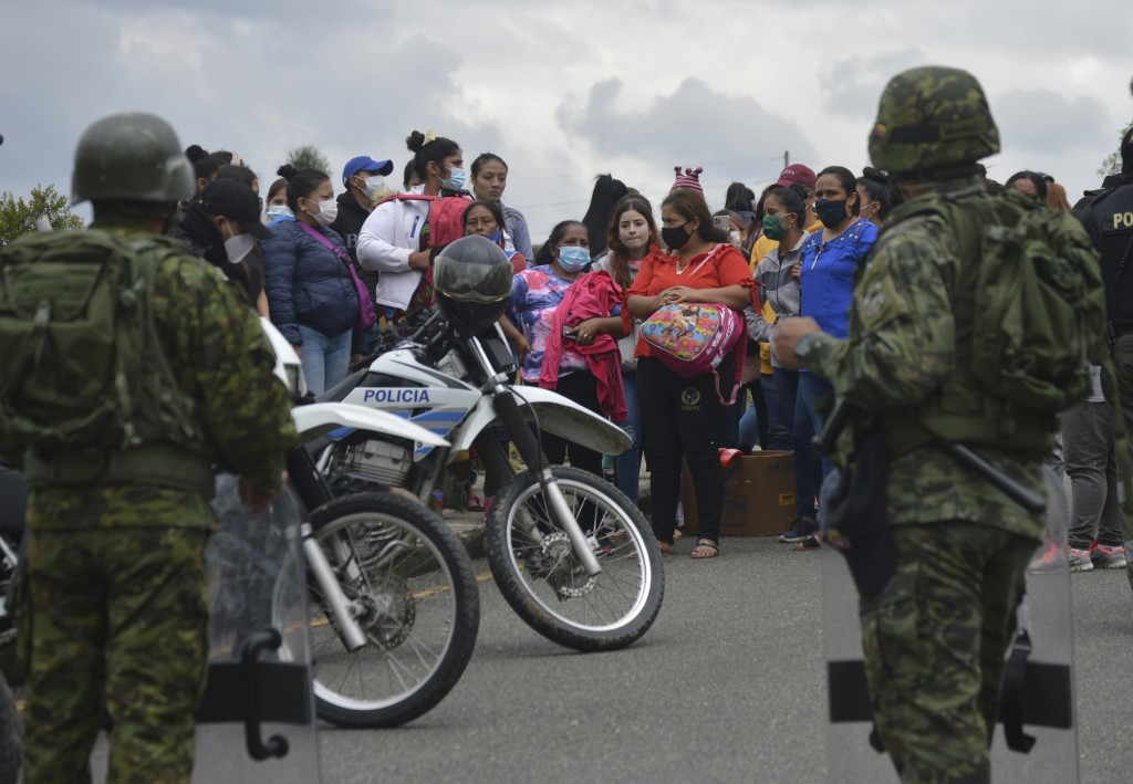 The relatives of prisoners gather outside Turi jail where soldiers stand guard after an inmate riot broke out in Cuenca, Ecuador, Tuesday, Feb. 23, 20...