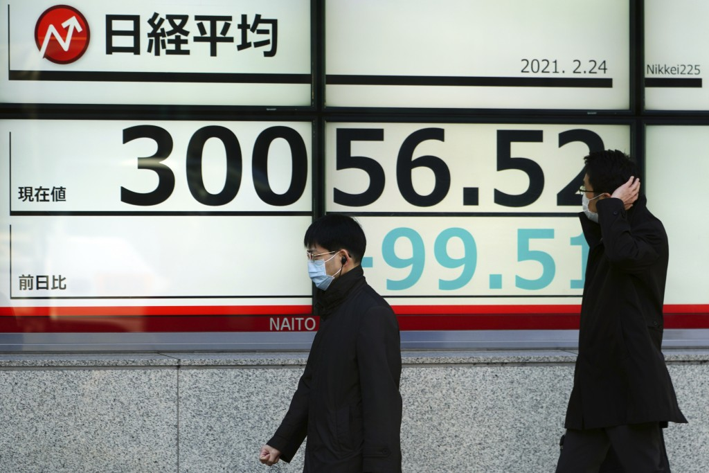 People wearing protective masks walk in front of an electronic stock board showing Japan's Nikkei 225 index at a securities firm Wednesday, Feb. 24, 2...