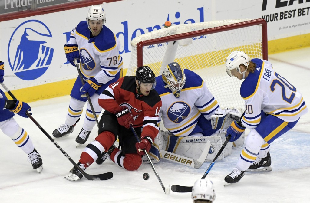 New Jersey Devils left wing Andreas Johnsson (11) attempts to get his stick on the puck as Buffalo Sabres goaltender Linus Ullmark (35) and center Cod...