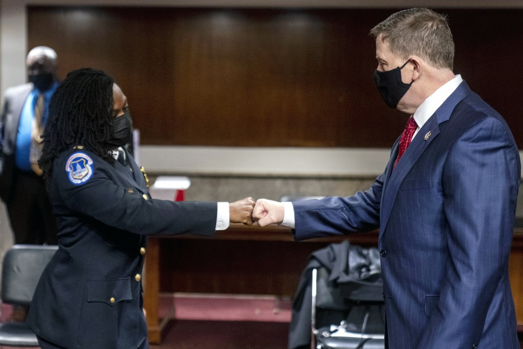 Former U.S. Capitol Police Chief Steven Sund, right, and Capitol Police Captain Carneysha Mendoza, left, greet each other before they testify before a...