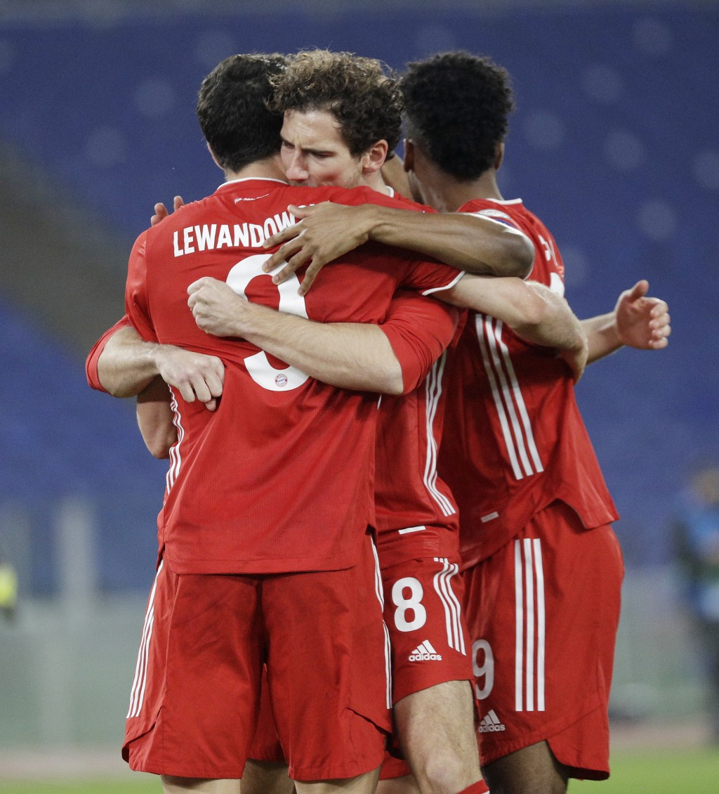 Bayern's Robert Lewandowski, left, celebrates with his teammates after scoring his side's opening goal during the Champions League round of 16 first l...