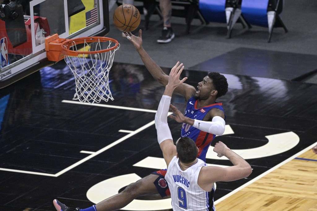 Detroit Pistons guard Josh Jackson (20) goes up for a shot in front of Orlando Magic center Nikola Vucevic (9) during the second half of an NBA basket...