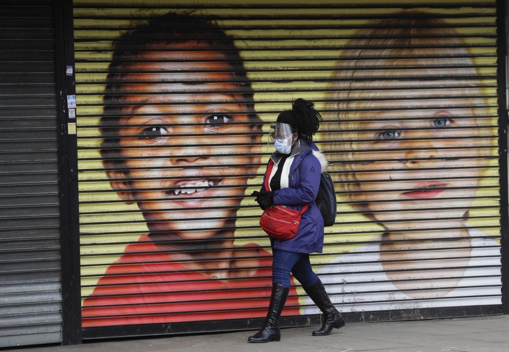 A woman wears protective face coverings as she passes the shutters of a closed shop in West Ealing in London. (AP Photo/Kirsty Wigglesworth)