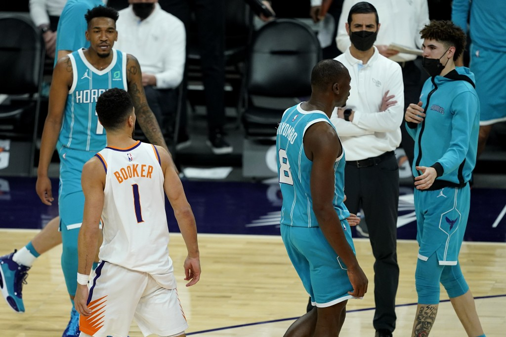 Phoenix Suns guard Devin Booker (1) has words with Charlotte Hornets guard LaMelo Ball, right, during the second half of an NBA basketball game, Wedne...