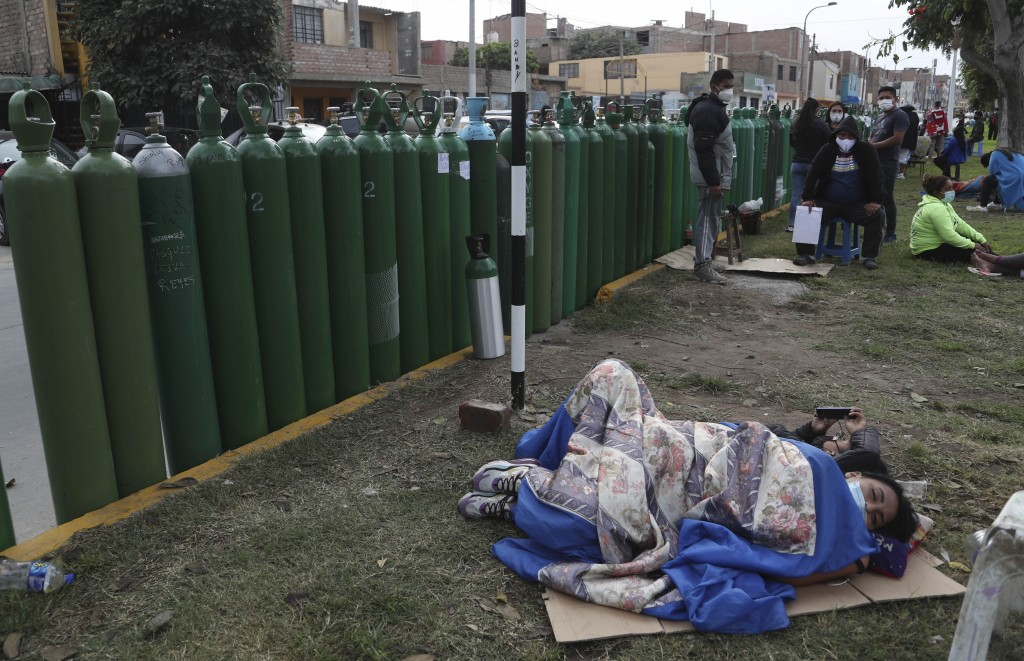 People lay next to their empty oxygen tanks as many wait for the refill shop to open in Callao, Peru, Monday, Jan. 25, 2021, amid the COVID-19 pandemi...
