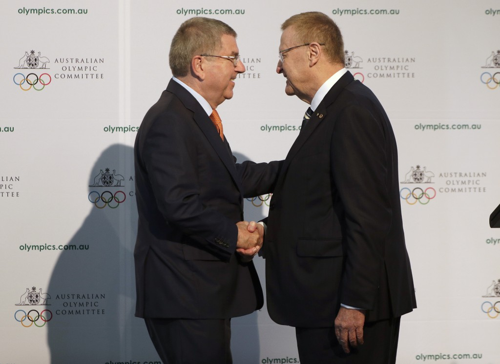 FILE - In this Saturday, May 4, 2019 file photo, International Olympic Committee President Thomas Bach, left, shakes hands with Australian Olympic Com...