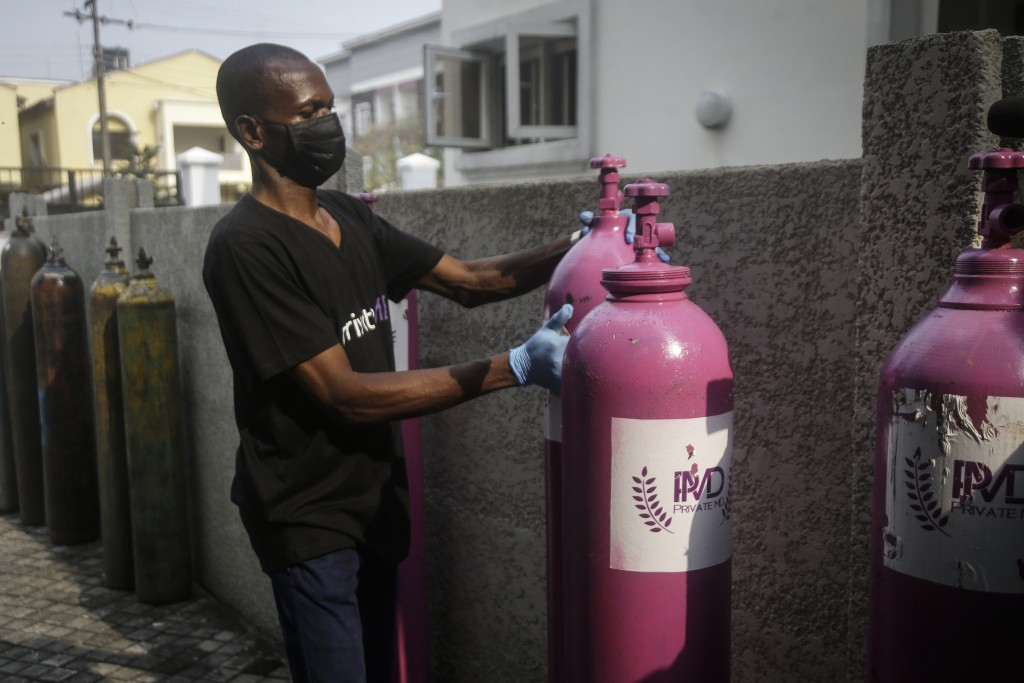 A worker from a private medical service brings oxygen bottles to aid the recovery of a COVID-19 patient, at her home in Lagos, Nigeria on Saturday, Fe...