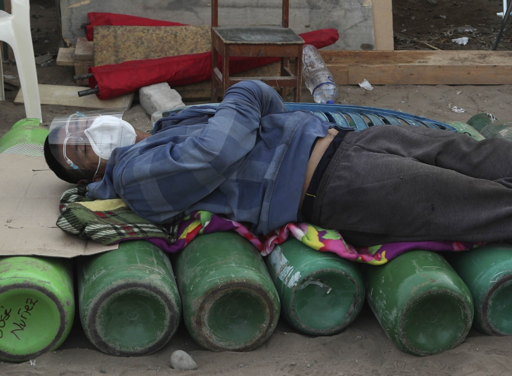 A man sleeps on top of empty oxygen cylinders, waiting for a shop to open to refill his tank, in the Villa El Salvador neighborhood of Lima, Peru, ear...