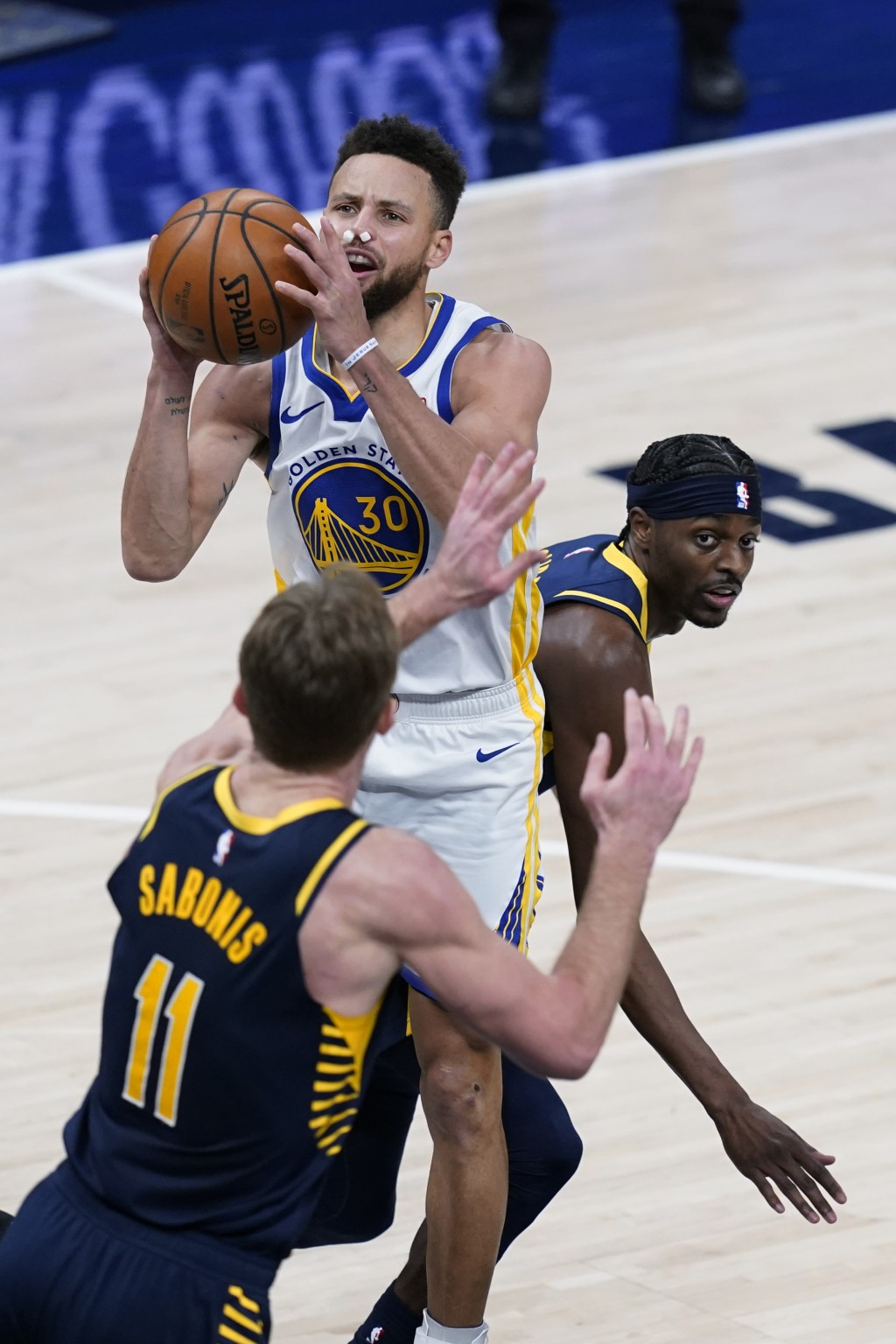 Golden State Warriors' Stephen Curry (30) shoots from between Indiana Pacers' Justin Holiday, right, and Domantas Sabonis during the second half of an...