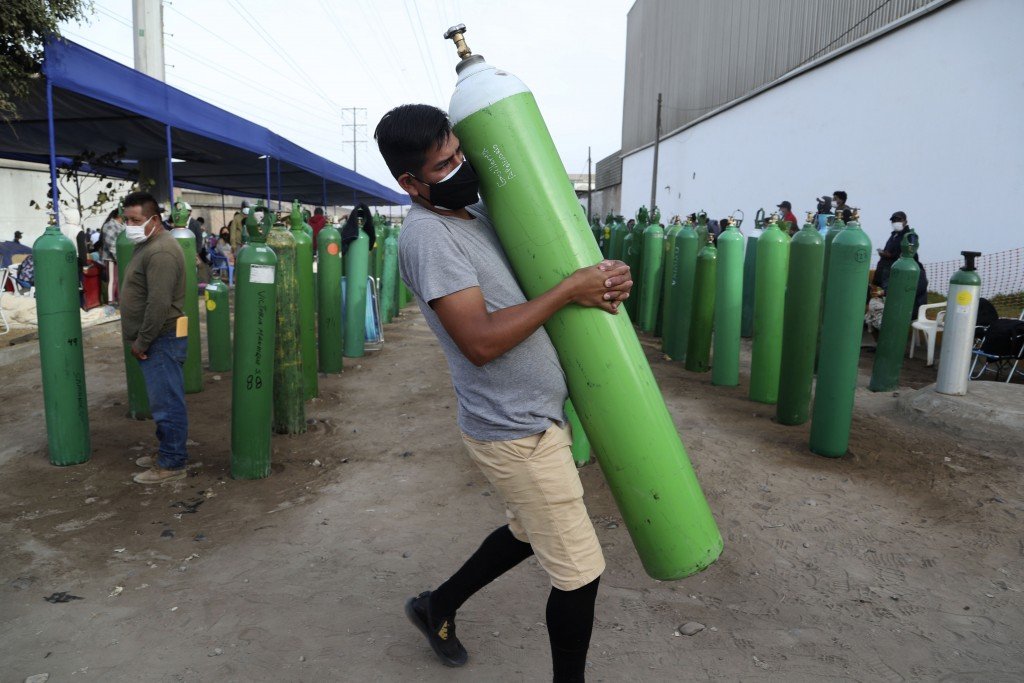 A man carries his empty oxygen tank to be filled after arriving at the head of the line, in the Villa El Salvador neighborhood of Lima, early Thursday...