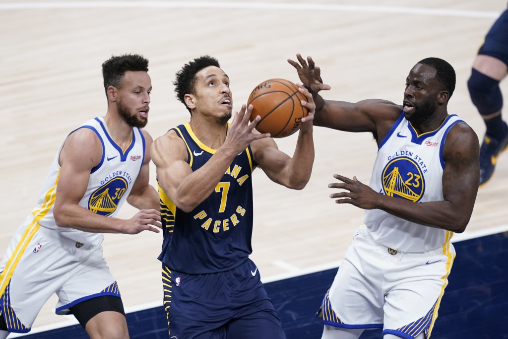 Indiana Pacers' Malcolm Brogdon (7) looks for a shot from between Golden State Warriors' Draymond Green (23) and Stephen Curry (30) during the first h...