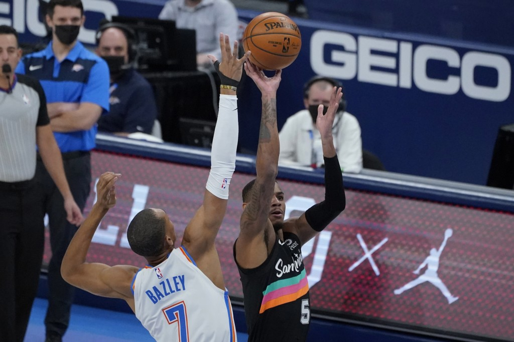 San Antonio Spurs guard Dejounte Murray (5) shoots as Oklahoma City Thunder forward Darius Bazley (7) defends during the first half of an NBA basketba...