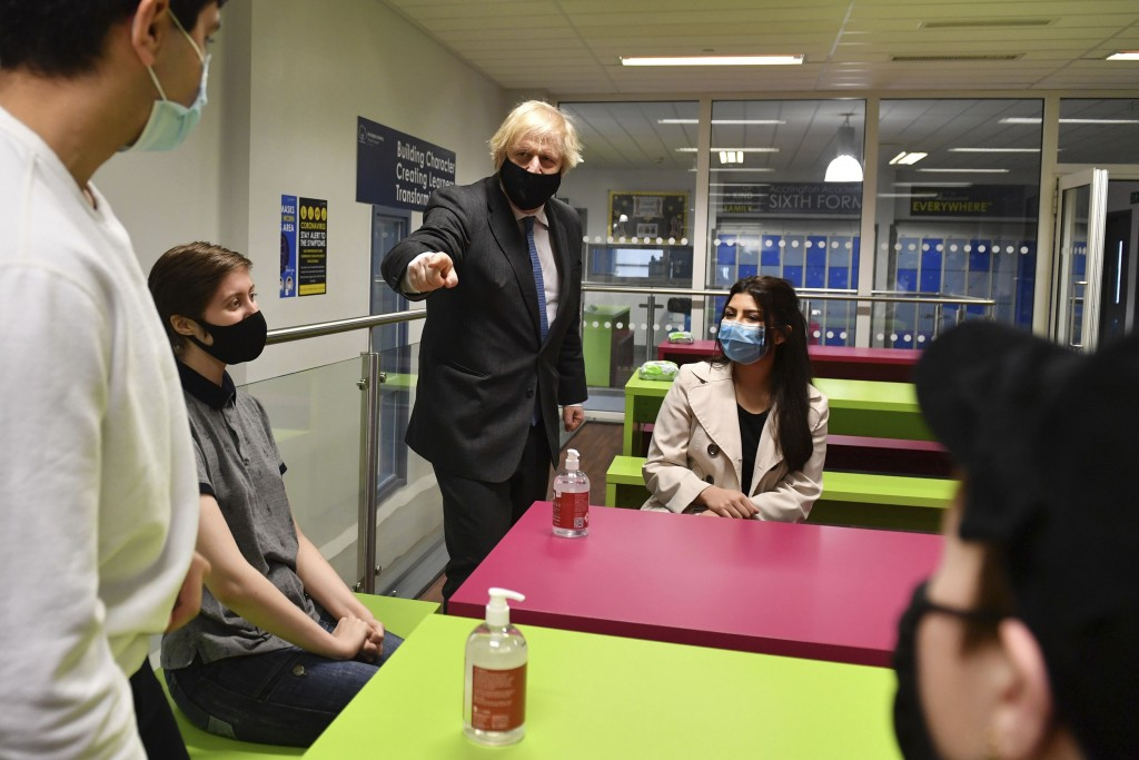 Britain's Prime Minister Boris Johnson, background centre left, meets Sixth form students during a visit to Accrington Academy in Accrington, England,...