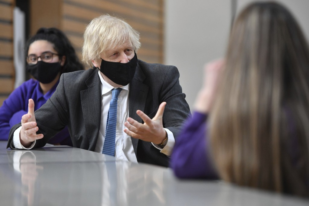 Britain's Prime Minister Boris Johnson meets with Year 11 students in the canteen during a visit to Accrington Academy in Accrington, England, Thursda...