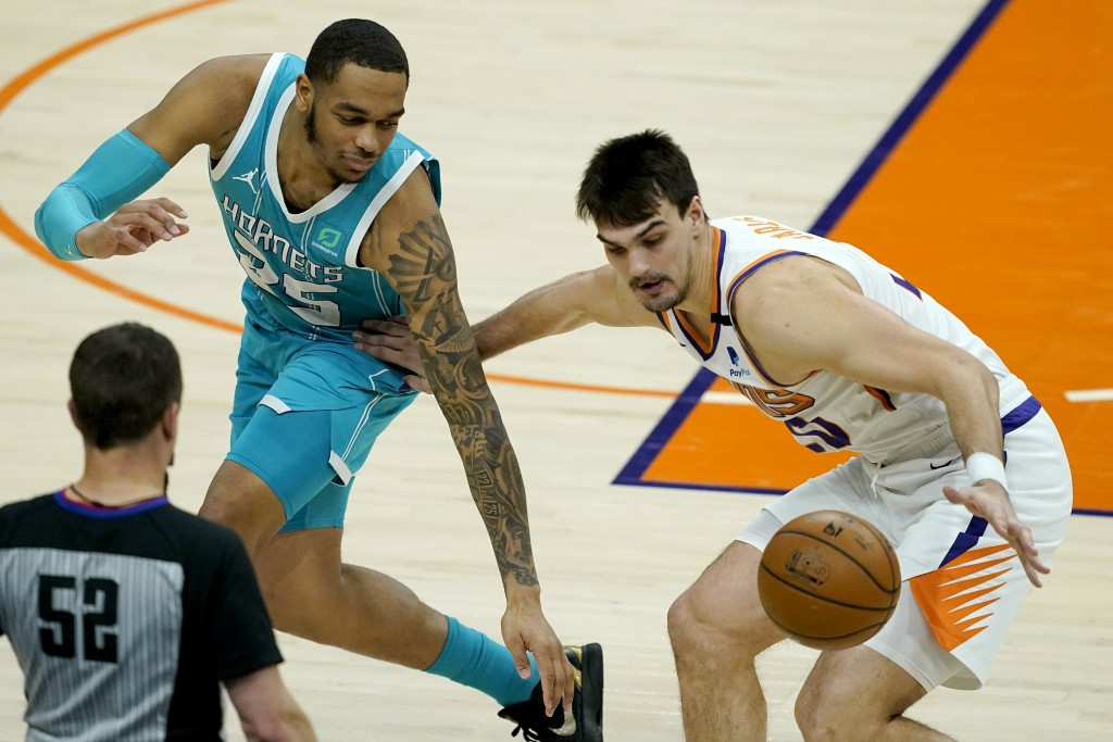 Phoenix Suns forward Frank Kaminsky, right, steals the ball from Charlotte Hornets forward P.J. Washington (25) during the first half of an NBA basket...