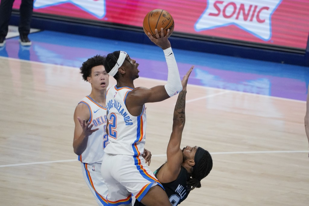 Oklahoma City Thunder guard Shai Gilgeous-Alexander (2) shoots over San Antonio Spurs guard Patty Mills, right, during the second half of an NBA baske...