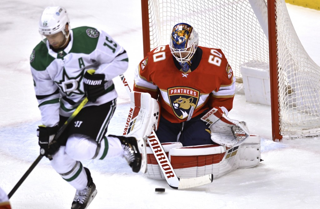 Florida Panthers goaltender Chris Driedger (60) makes a save behind a screen by Dallas Stars' Blake Comeau (15) during the first period of an NHL hock...