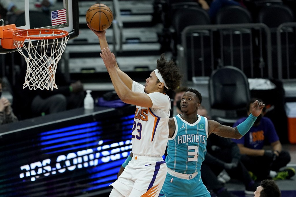 Phoenix Suns forward Cameron Johnson (23) shoots past Charlotte Hornets guard Terry Rozier (3) during the first half of an NBA basketball game, Wednes...