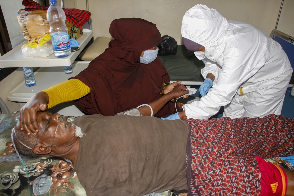 A doctor tends to a patient on oxygen suffering from COVID-19 in a ward for coronavirus patients at the Martini hospital in Mogadishu, Somalia on Wedn...