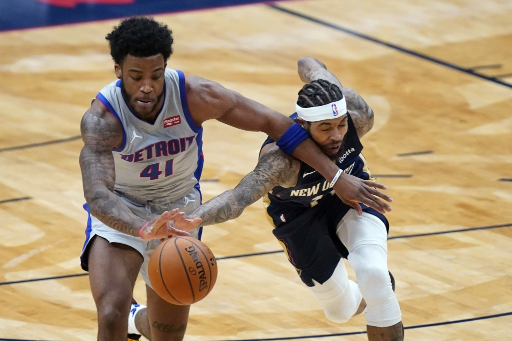 Detroit Pistons forward Saddiq Bey (41) and New Orleans Pelicans forward Brandon Ingram reach for the ball during the first half of an NBA basketball ...