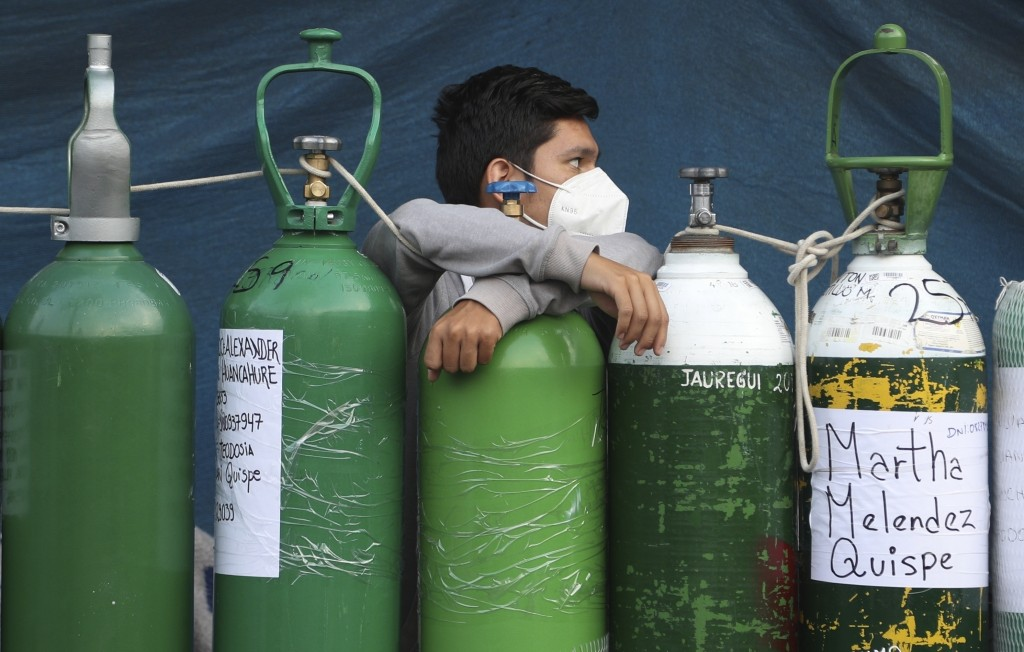 A youth rests on his empty oxygen cylinder waiting for a refill shop to open in the San Juan de Lurigancho neighborhood of Lima, Peru, Monday, Feb. 22...