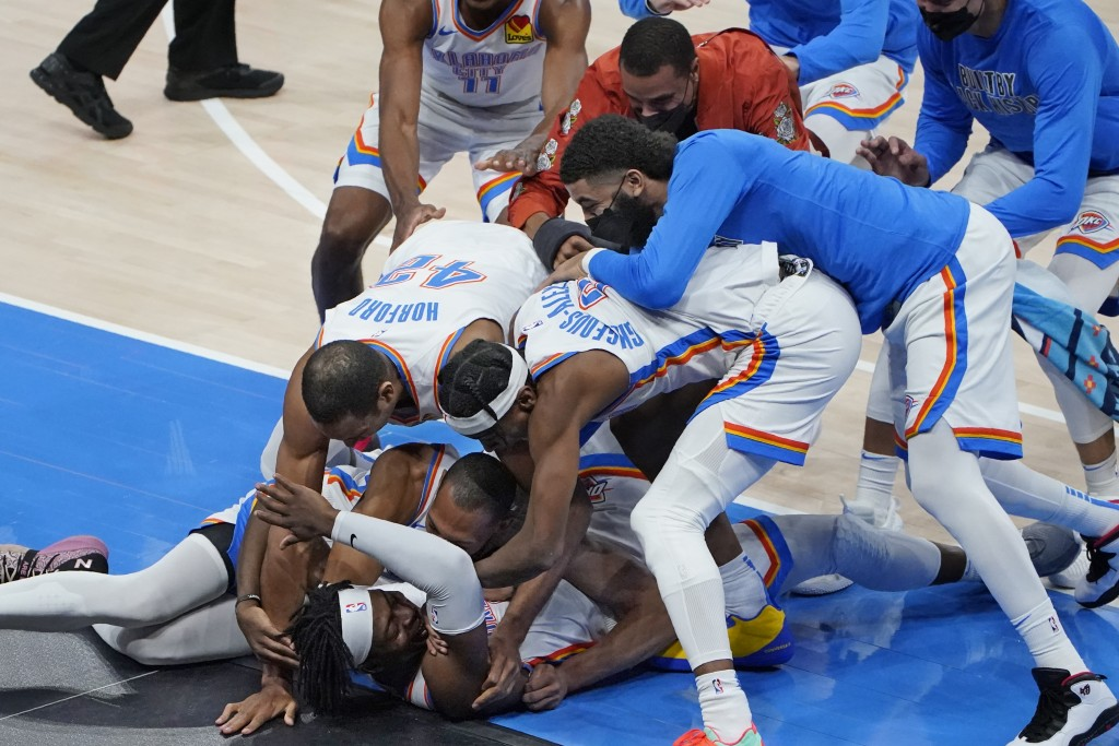 Oklahoma City Thunder forward Luguentz Dort, bottom, is mobbed by teammates after hitting the game-winning shot in an NBA basketball game against the ...