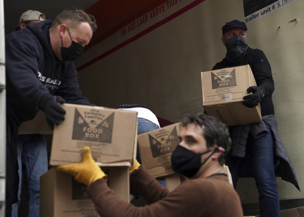 Volunteers unload boxes of food from a truck for a distribution program run through Mosaic West Queens Church in the Sunnyside neighborhood of the Que...