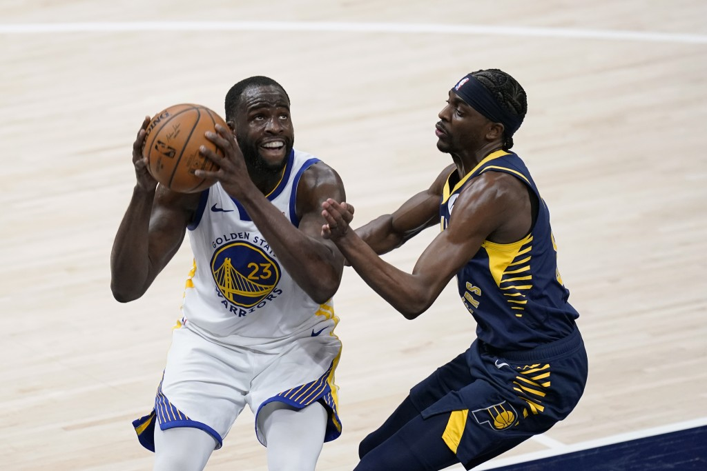 Golden State Warriors' Draymond Green (23) goes to the basket against Indiana Pacers' Justin Holiday during the second half of an NBA basketball game ...