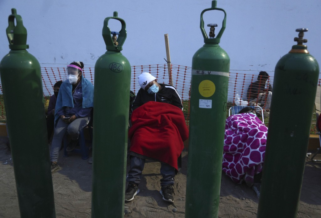 People sleep framed by their empty oxygen cylinders waiting for a shop to open to refill their tanks, in the Villa El Salvador neighborhood of Lima, e...