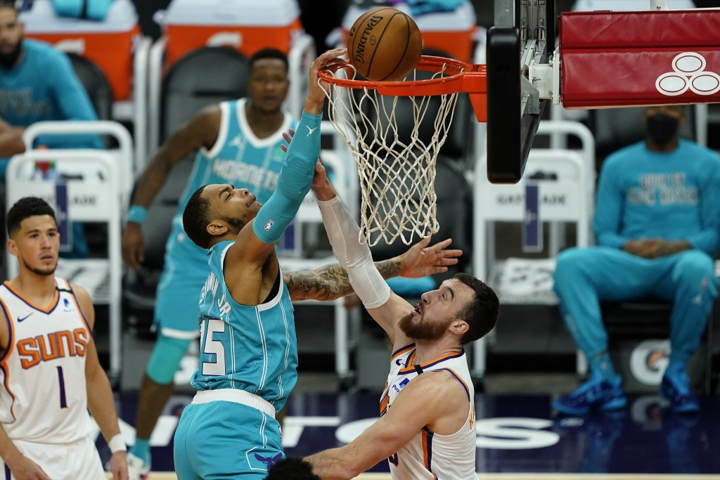 Charlotte Hornets forward P.J. Washington is fouled by Phoenix Suns forward Frank Kaminsky, right, during the first half of an NBA basketball game, We...