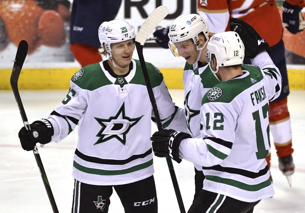 Dallas Stars defenseman Esa Lindell (23) celebrates a goal with teammates Joel Kiviranta (25) and Radek Faksa (12) during the third period of an NHL h...