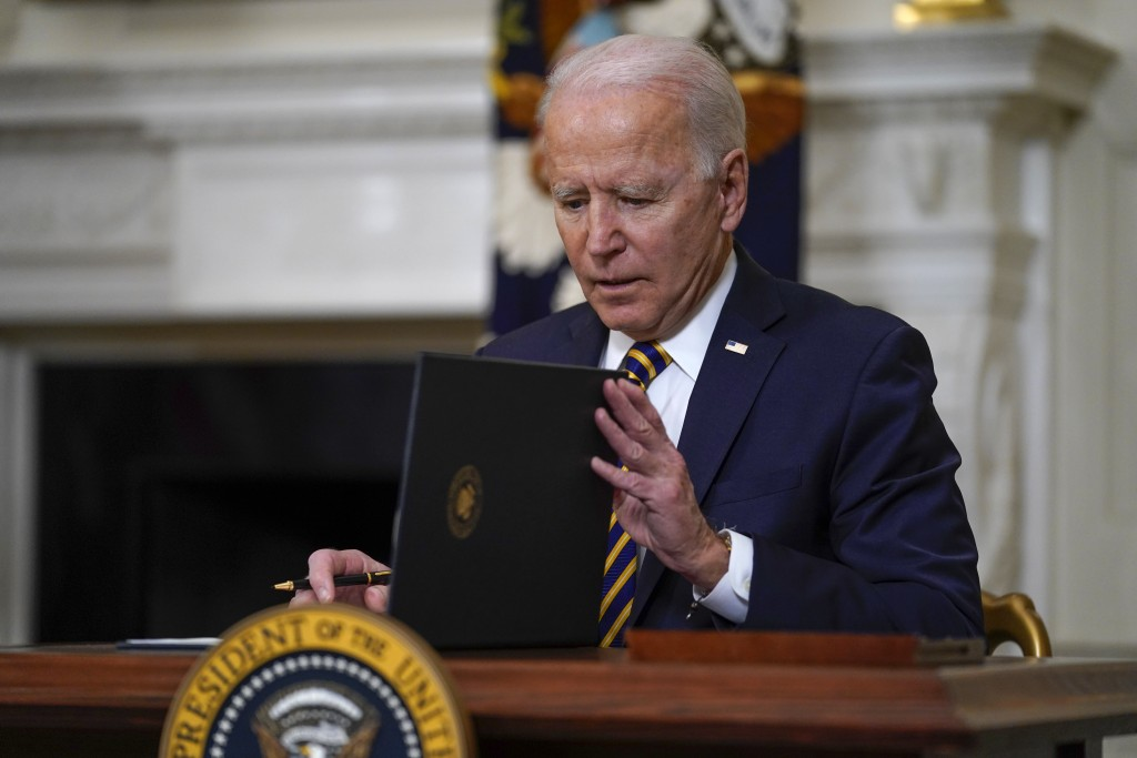 President Joe Biden closes the folder after signing an executive order relating to U.S. supply chains, in the State Dining Room of the White House, We...