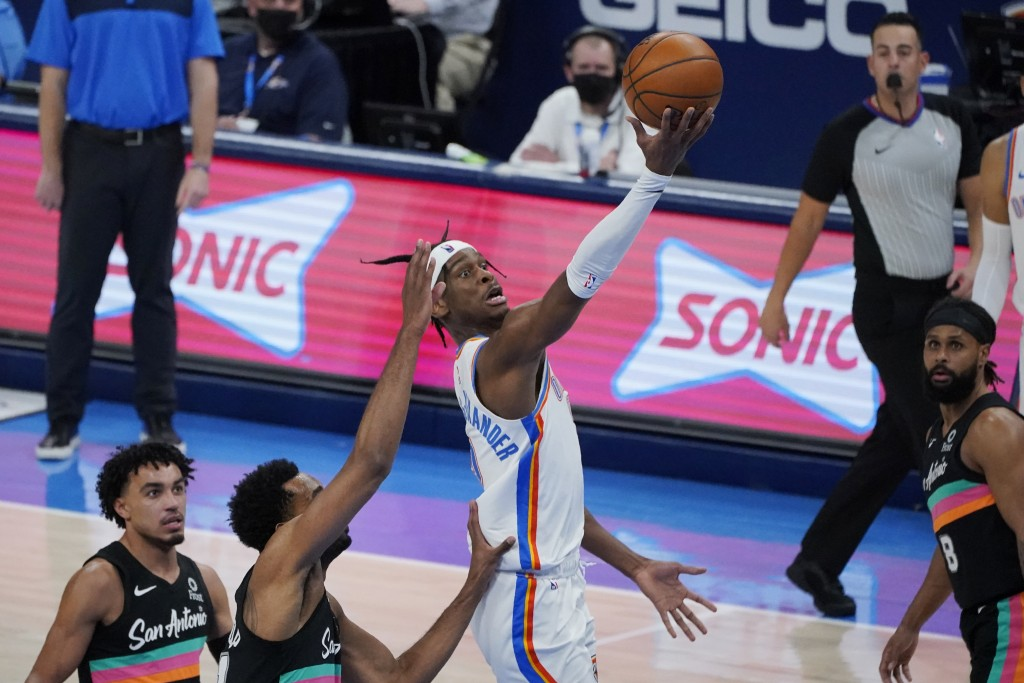 Oklahoma City Thunder guard Shai Gilgeous-Alexander shoots between San Antonio Spurs guard Tre Jones, left, forward Trey Lyles, second from left, and ...