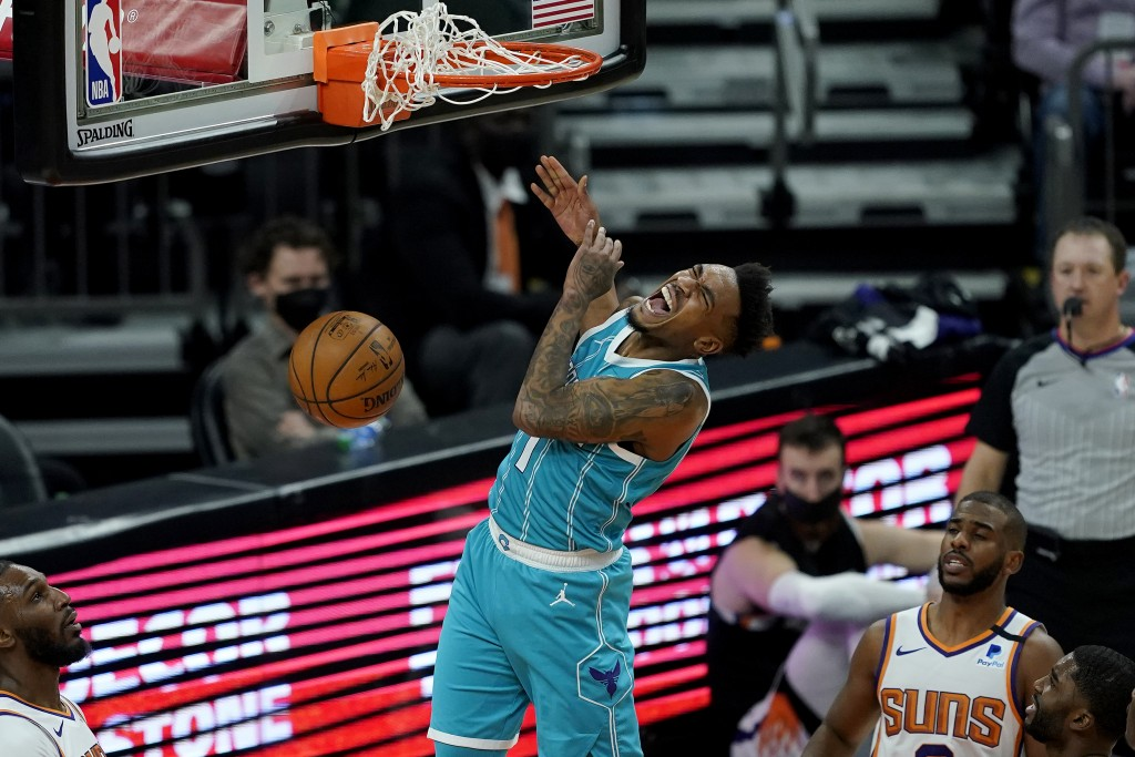 Charlotte Hornets guard Malik Monk (1) dunks against the Phoenix Suns during the second half of an NBA basketball game, Wednesday, Feb. 24, 2021, in P...