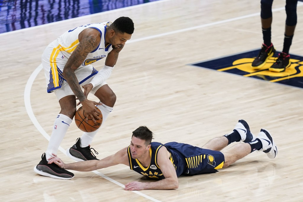 Indiana Pacers' T.J. McConnell (9) dives for a loose ball against Golden State Warriors' Kent Bazemore during the first half of an NBA basketball game...