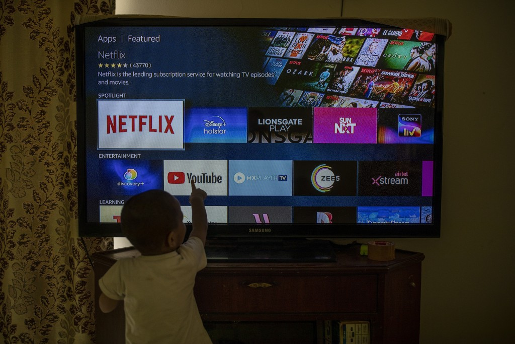 A child touches a TV screen displaying OTT streaming apps at his home in New Delhi, India, Thursday, Feb. 25, 2021. India has rolled out new regulatio...
