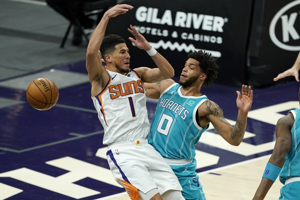 Charlotte Hornets forward Miles Bridges (0) knocks the ball loose from Phoenix Suns guard Devin Booker (1) during the first half of an NBA basketball ...