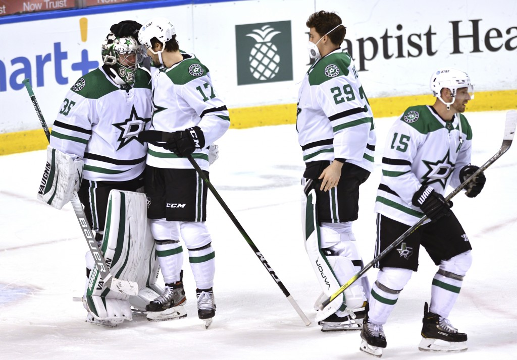 Dallas Stars goaltender Anton Khudobin (35) is congratulated by Nick Caamano (17) and teammates following a win over the Florida Panthers in an NHL ho...