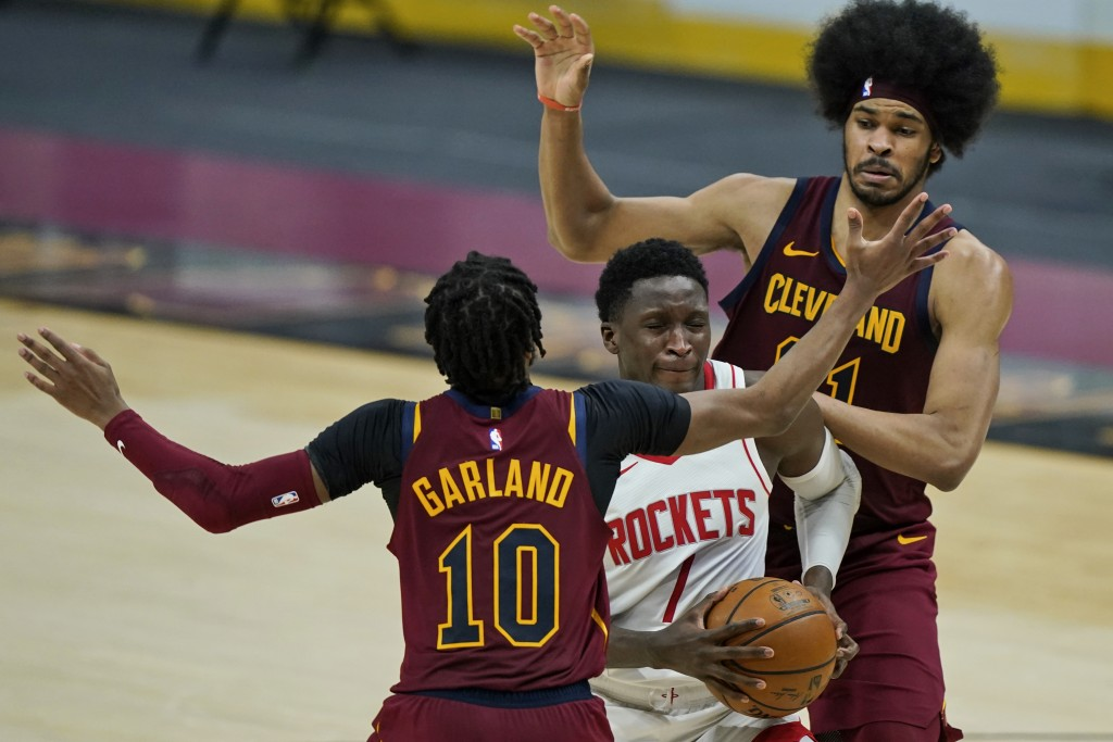 Houston Rockets' Victor Oladipo, center, drives to the basket between Cleveland Cavaliers' Jarrett Allen, right, and Cleveland Cavaliers' Darius Garla...