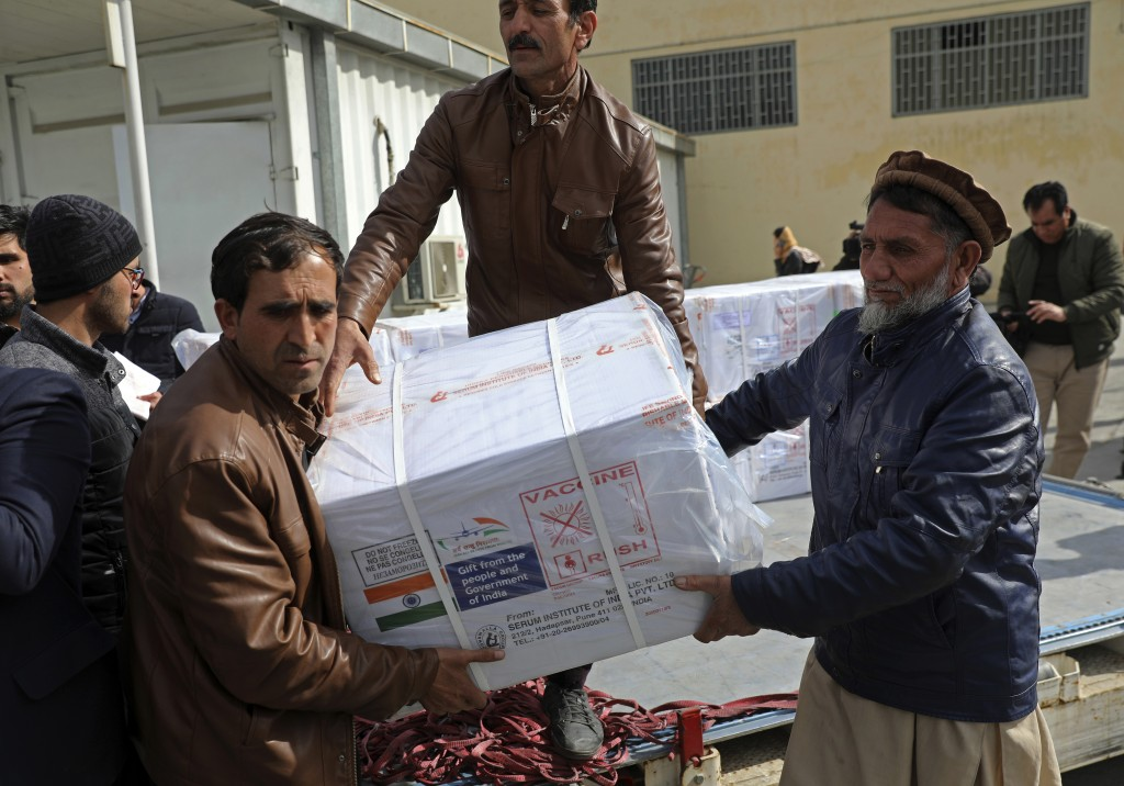 FILE - In this Feb. 7, 2021, file photo, Afghan health ministry workers unload boxes of the first shipment of 500,000 doses of the AstraZeneca coronav...