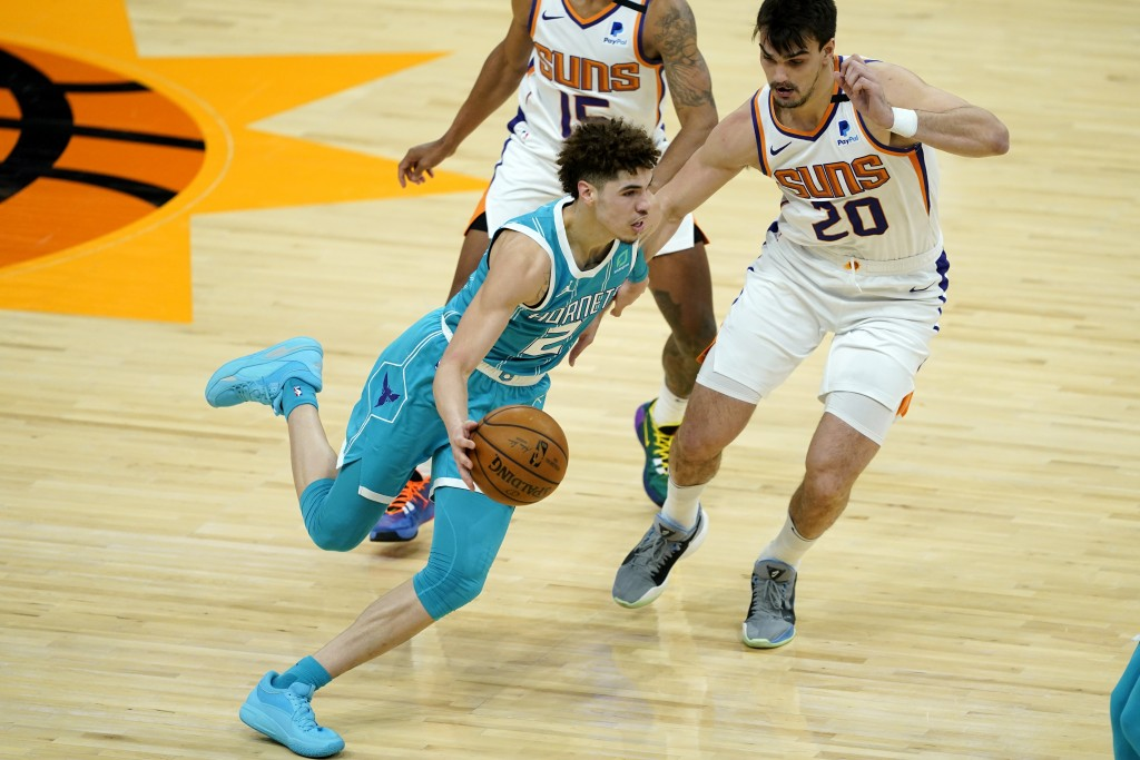 Charlotte Hornets guard LaMelo Ball (2) drives as Phoenix Suns forward Dario Saric (20) defends during the first half of an NBA basketball game, Wedne...