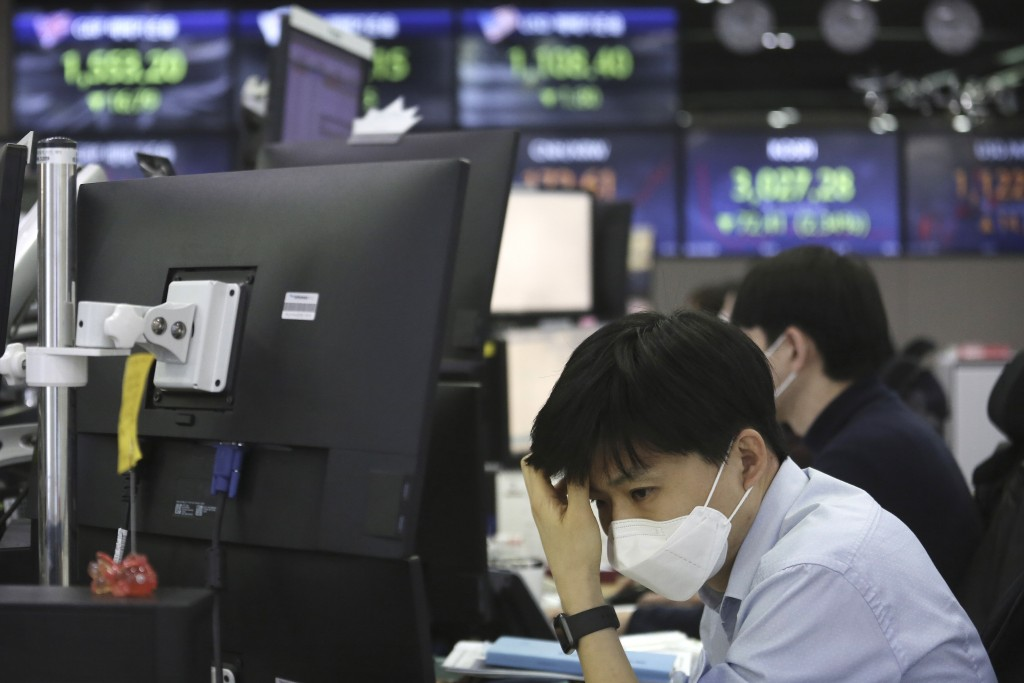 A currency trader watches monitors at the foreign exchange dealing room of the KEB Hana Bank headquarters in Seoul, South Korea, Friday, Feb. 26, 2021...