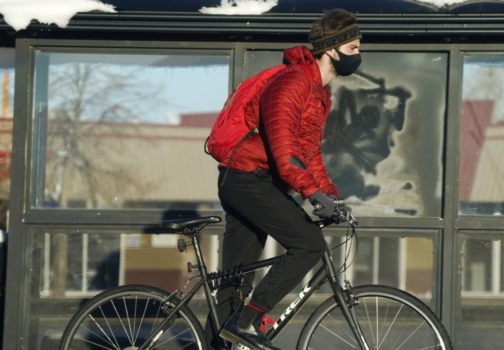 A cyclist wears a face mask while riding on a trail after more than a foot of snow was left by a late winter storm that swept over the region Thursday...