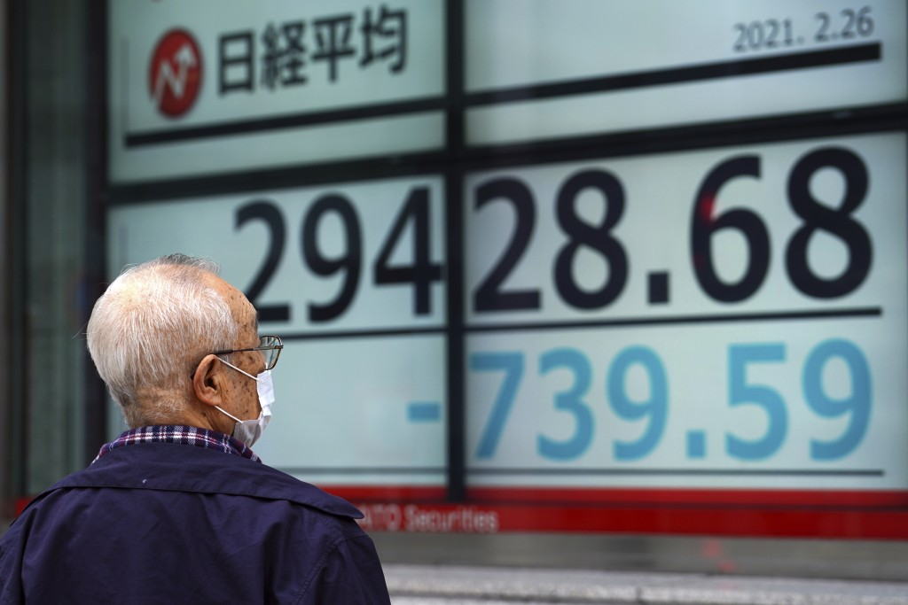 A man wearing a protective mask looks at an electronic stock board showing Japan's Nikkei 225 index at a securities firm Friday, Feb. 26, 2021, in Tok...