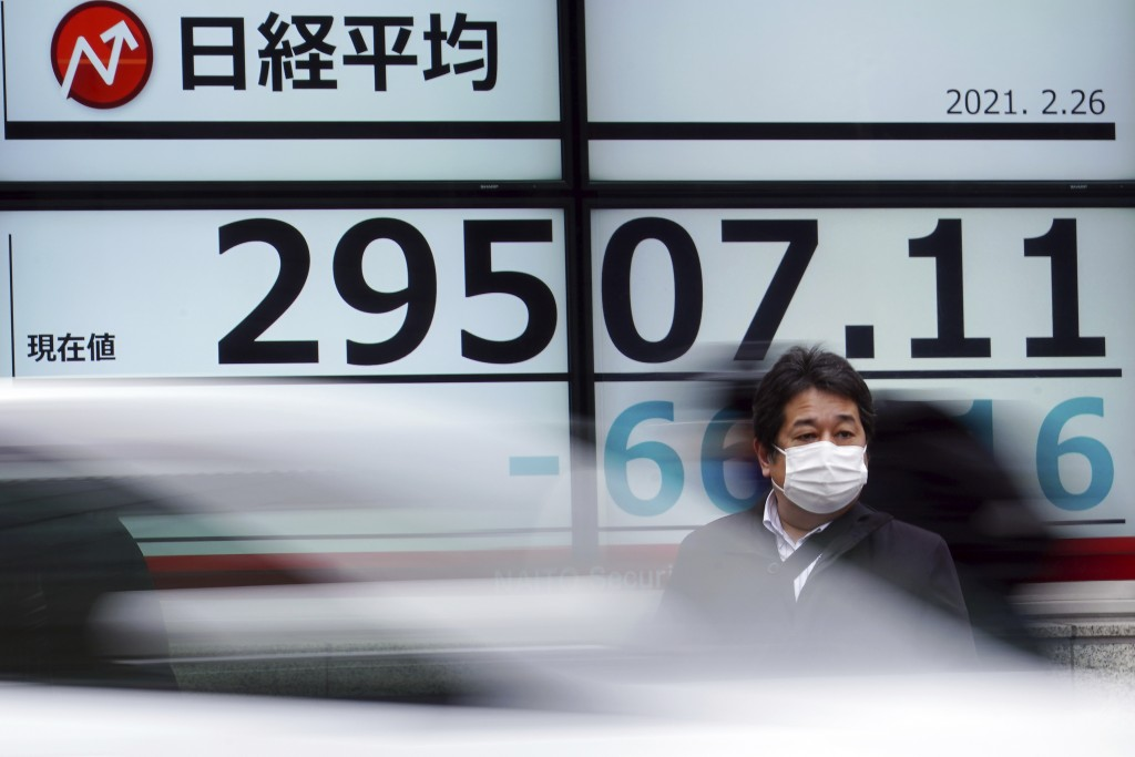 A man wearing a protective mask stands in front of an electronic stock board showing Japan's Nikkei 225 index at a securities firm Friday, Feb. 26, 20...